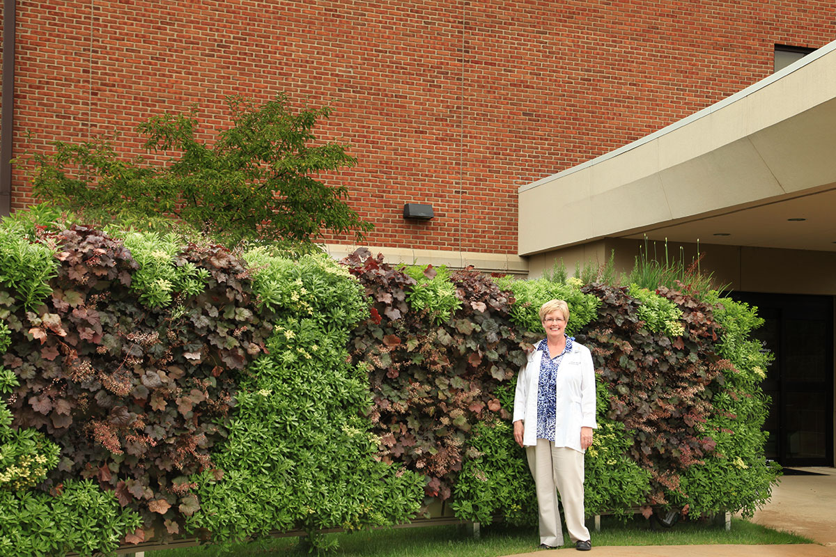 Nurse at heart clinic smiles in front of outdoor heart-shaped plantings in vertical garden.