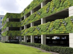Modern four level parking garage is located next to an office building.