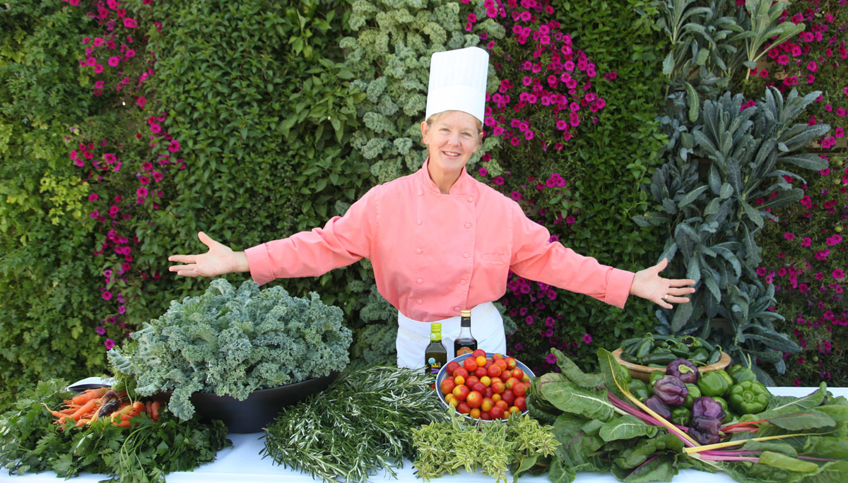 Woman Chef with bountiful harvest of edibles grown on a vertical garden.