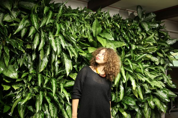 A woman admires a green living wall illuminated by a LiveWall Norb LED light.