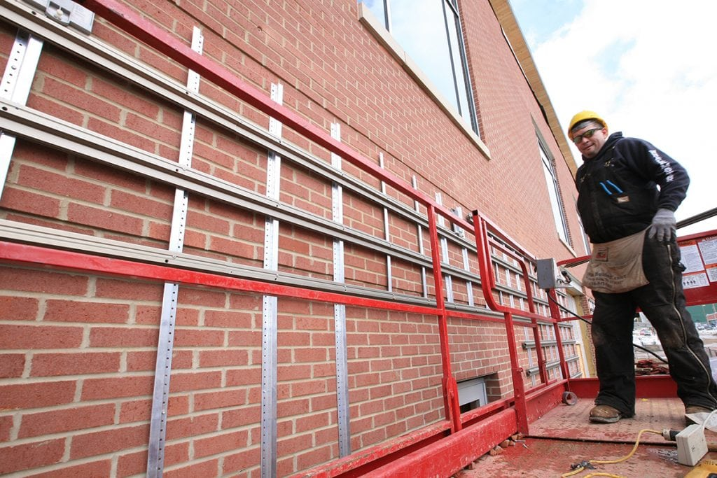 Man on a platform installing LiveWall furring strips and RainRails on the side of a red brick building.