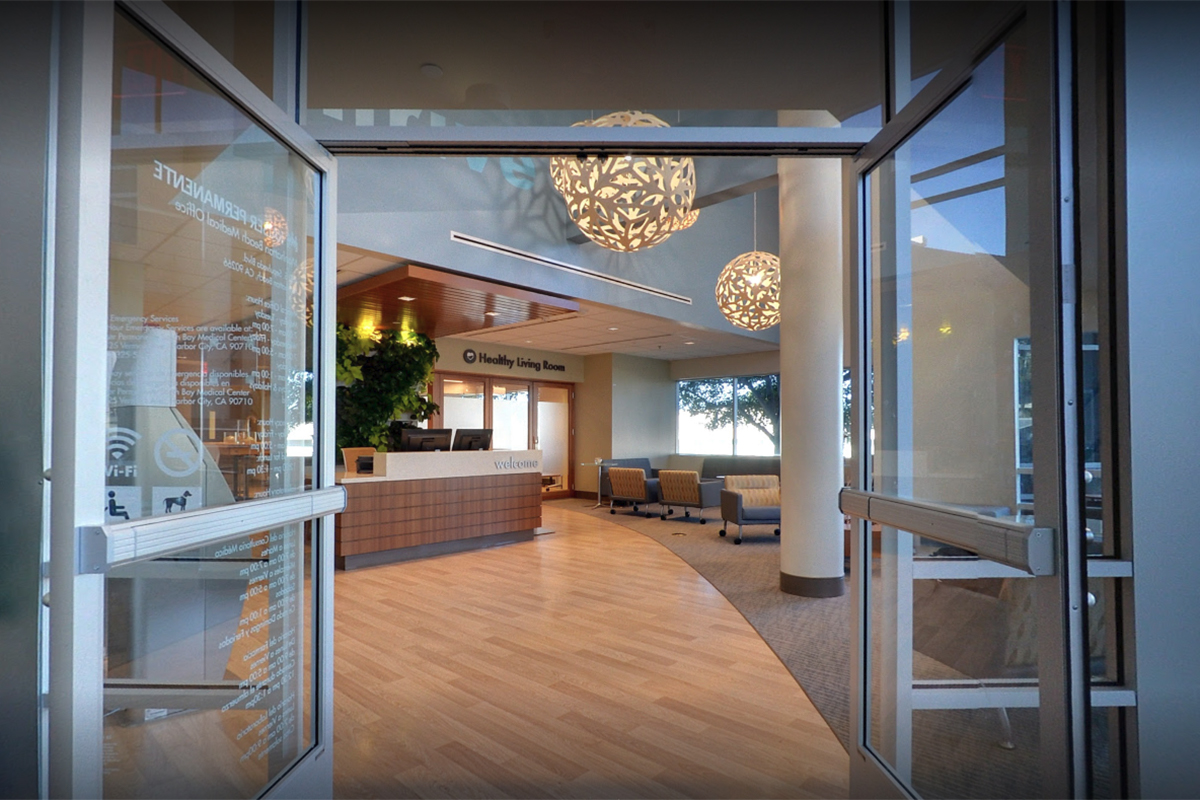 The entrance to Kaiser Permanente medical office with soft lighting features and a planted wall.