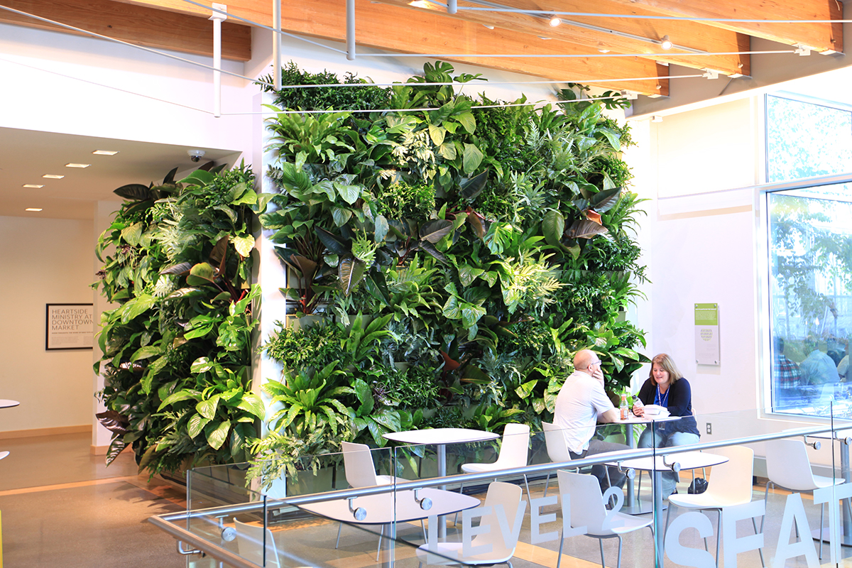 Indoor living wall with seating area in mixed-use space above restaurants and retail.