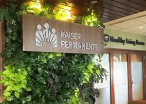 Tropicals in a living wall serve as a backdrop to a Kaiser Permanente health care sign.