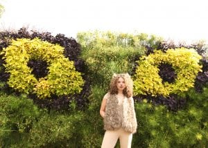 Living wall planted in shape of cat eyes with woman wearing lion Halloween costume.