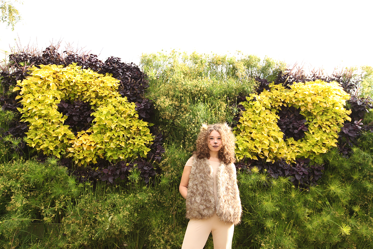 Living wall planted in shape of cat eyes with woman wearing Lion ...