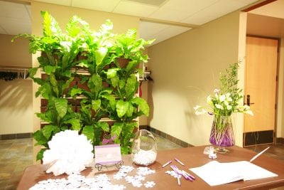 Wedding welcome table with living wall backdrop.