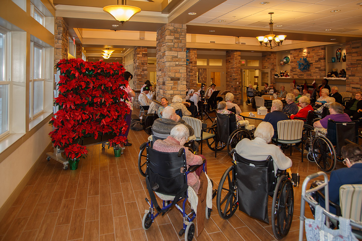 Residents of Kahl Home enjoy a poinsettia vertical garden during a holiday party.