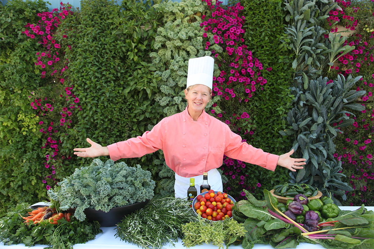 Culinary teacher demonstrates ultra fresh produce from vertical gardening.