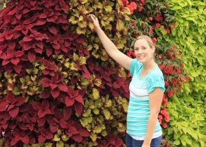 Woman admiring a LiveWall living wall planted with red and green coleus.
