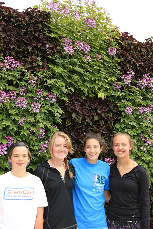 Nursery interns in front of a wall with Cleome and Coleus.