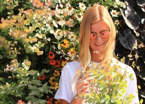 Woman in sunglasses in front of a colorful annual LiveWall with eucalyptus and zinnias.