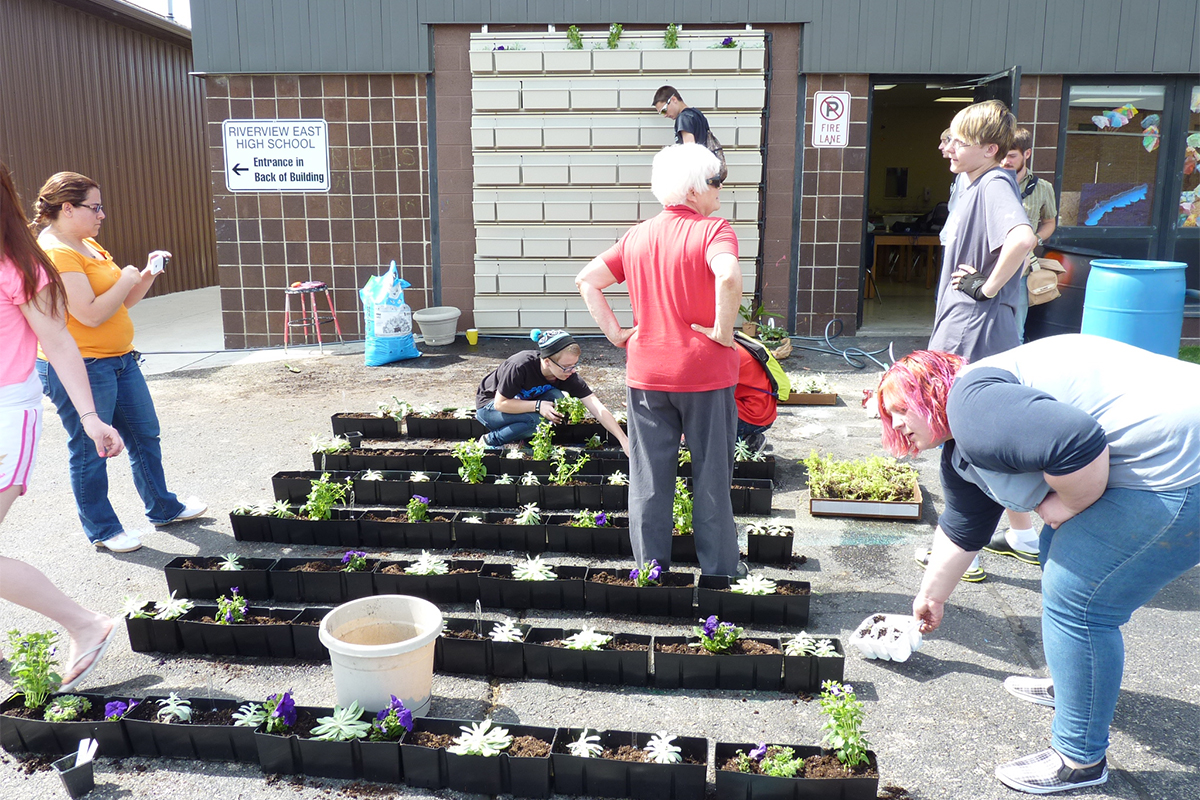 Student installation of LiveWall planters at Riverview East High School.
