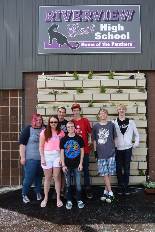 Proud students at Riverview East High School, after installing starter plants into their green wall system.