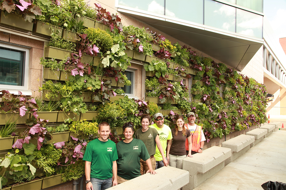 People smiling in front of a newly-planted LiveWall at the Rapid Central Station in Grand Rapids, MI.