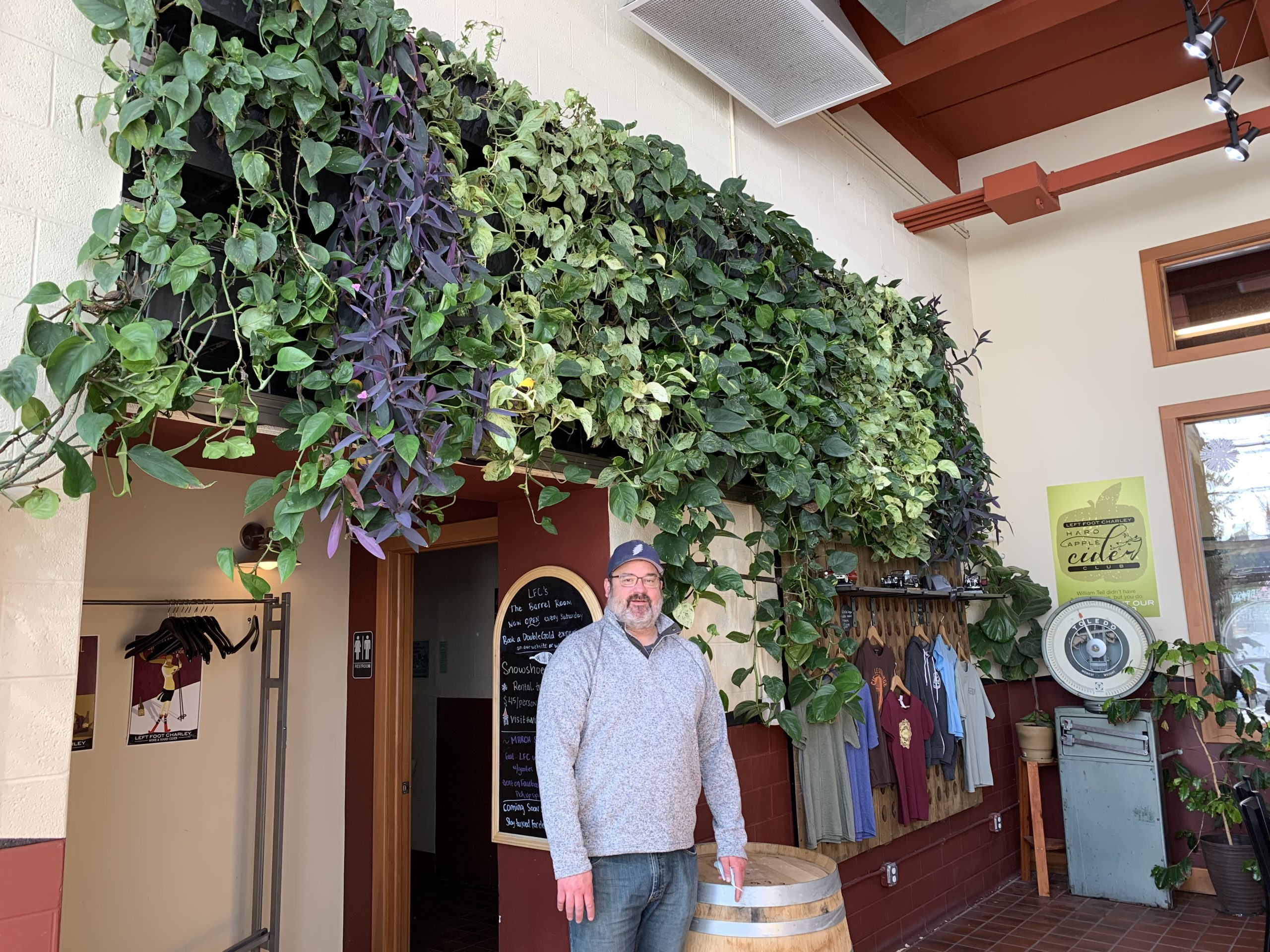 Left Foot Charley owner Bryan Ulbrich standing under his winery's green wall