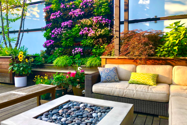 A colorful, vibrant living wall on a wood deck with patio furniture and fireplace.