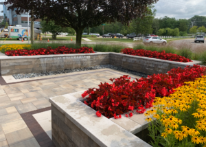 Red and yellow flowers planted in a LiveWall living wall system. Stone patio and fountain running.